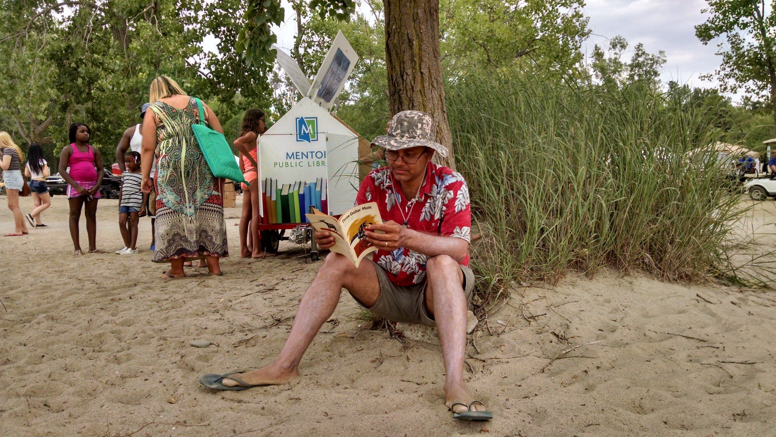 A man reads a book he found on Mentor Public Library's Pop-Up Library during BeachFest at Mentor Headlands Beach.