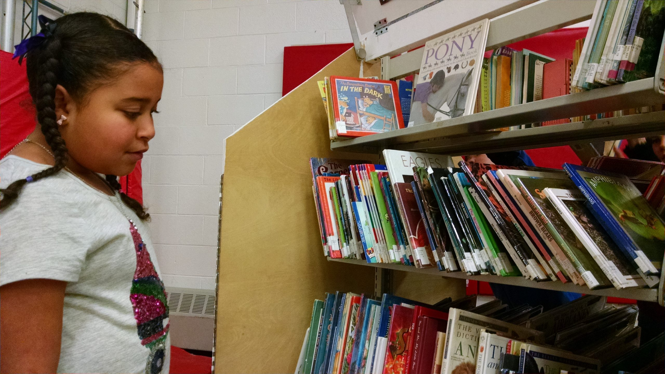 A student from Garfield Elementary mulls which book to take from the Pop-Up Library.